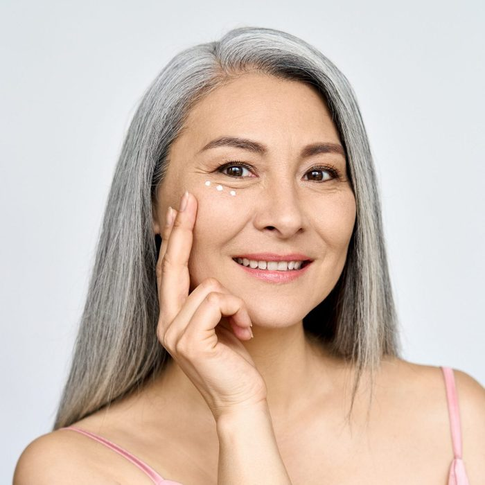 Happy middle aged mature asian woman headshot portrait. Skin care, eye care ads