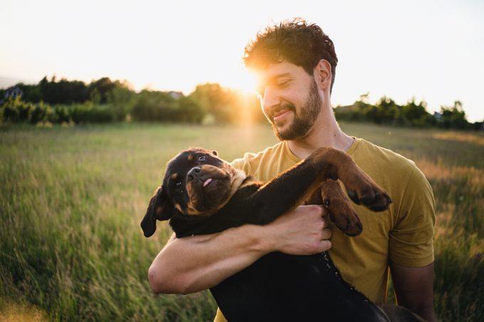 Man holding a Rottweiler puppy dog