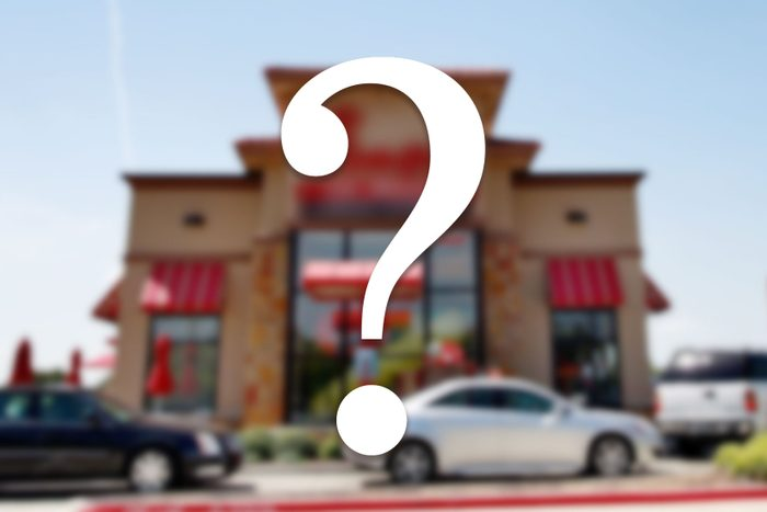 a blurred image of a restaurant facade with cars in the drive thru with a question mark overlay