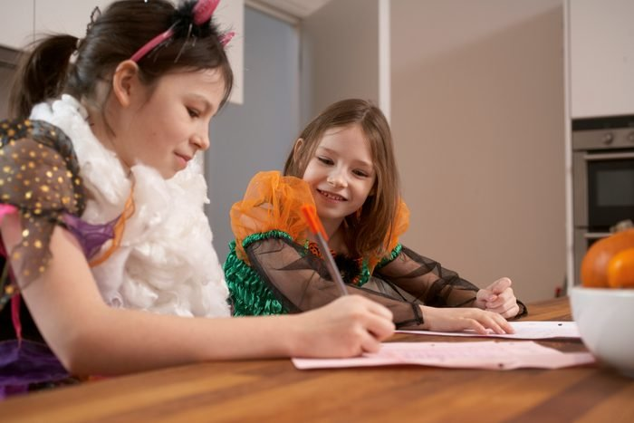 young girls in halloween costumes writing down movie quotes for party game