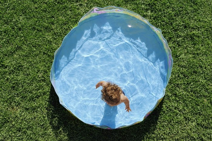 overhead view of little girl in baby pool outside