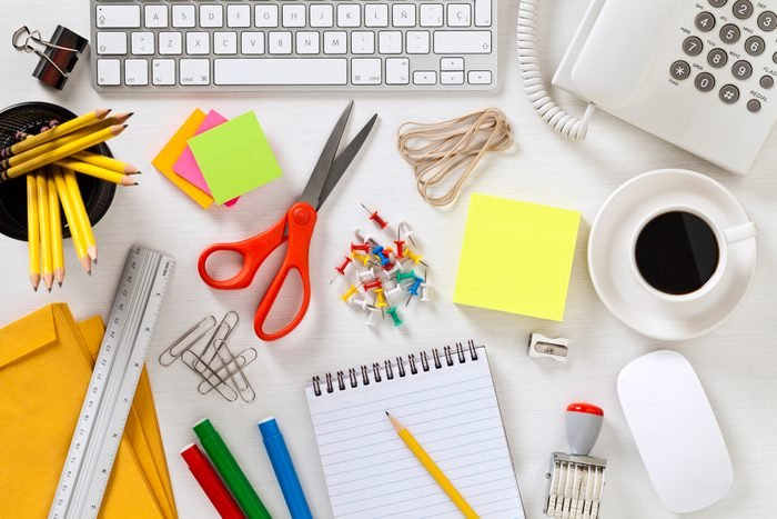 Office supplies and gadgets on gray desktop shot directly above