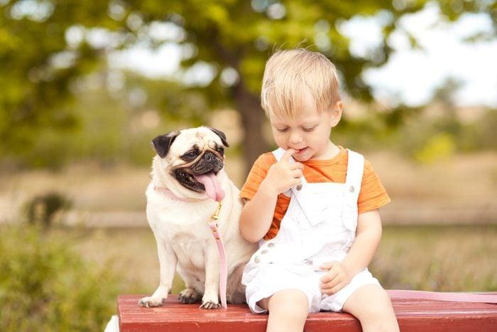 Cute baby boy sitting with pug