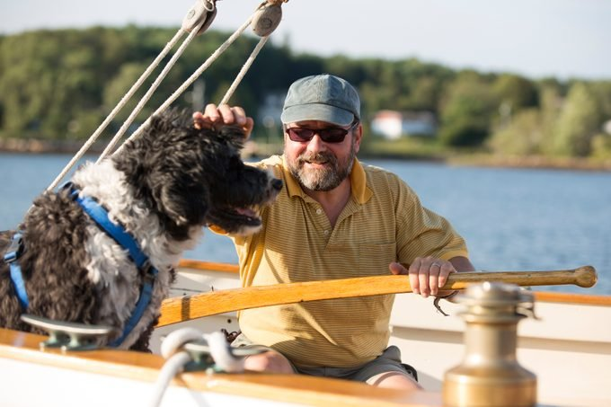 Man and his Portuguese water dog on a sailboat