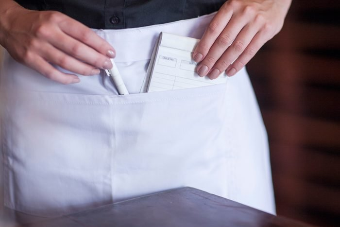 Waitress putting pen and notebook into pocket of apron