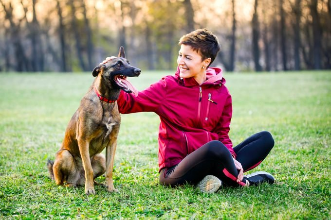 Young woman enjoying time outdoors with her belgian malinois dog pet.