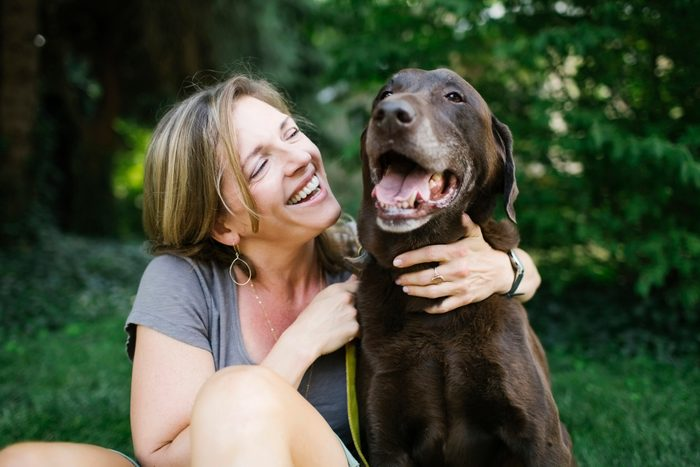 woman outside with labrador retriever smiling