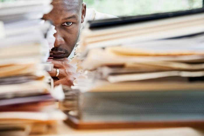 African businessman hiding behind stack of paperwork