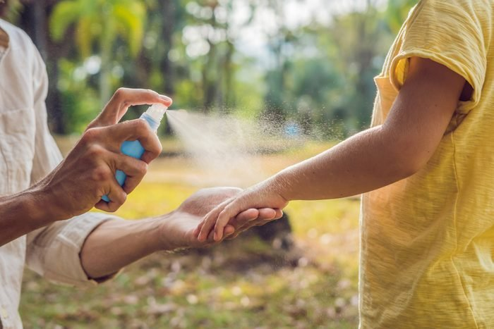 dad and son use mosquito spray.Spraying insect repellent on skin outdoor