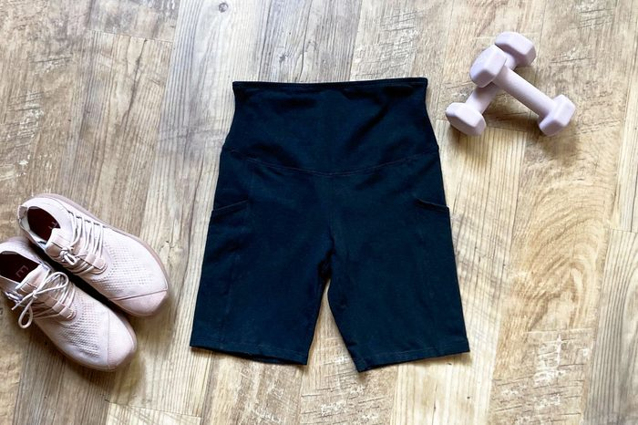 Yummie Bike Shorts in black on wood background with hand weights and sneakers