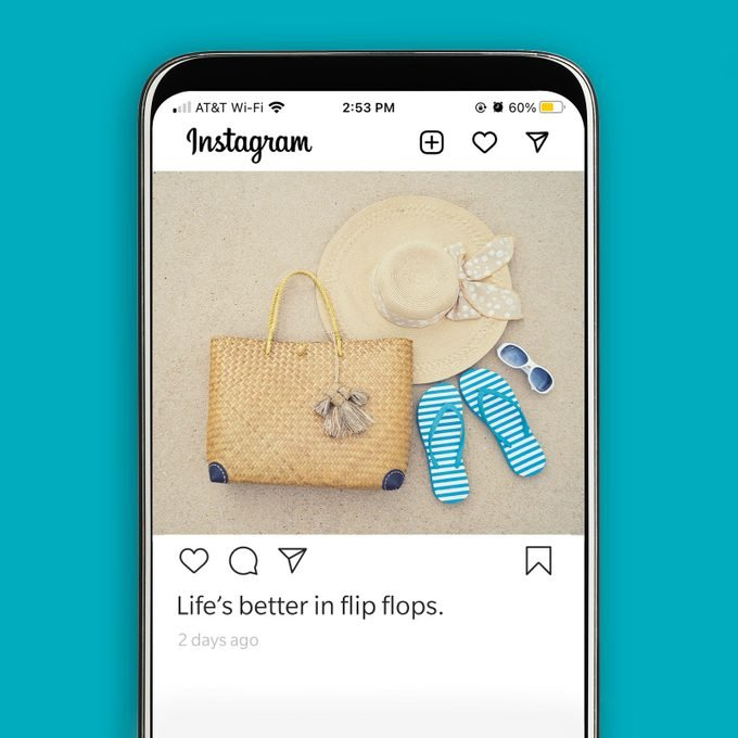 instagram screenshot displaying a flat lay image of a tote bag, hat and flip flops