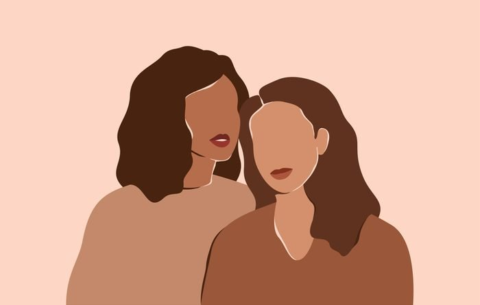 Two beautiful women with different skin colors stand together. Abstract minimal portrait of two girls in earth's natural tones. Concept of sisterhood and females friendship.