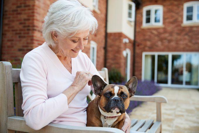 Senior Woman Sitting On Bench With Pet French Bulldog