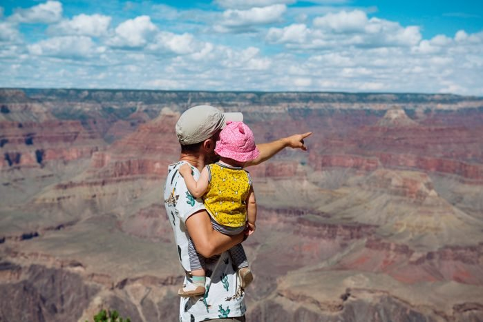 USA, Arizona, Grand Canyon National Park, father and baby girl enjoying the view, rear view