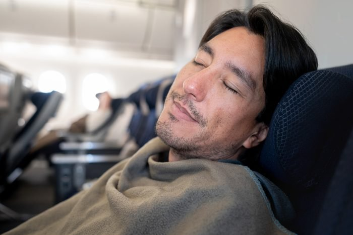 Man traveling by plane and sleeping