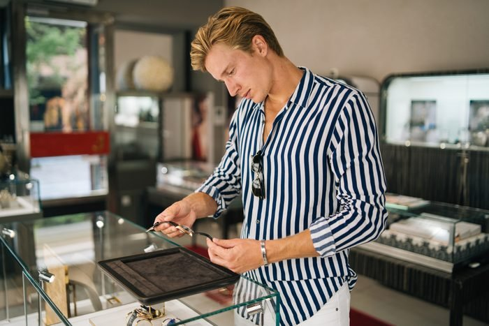 Young man smiles while shopping for watch
