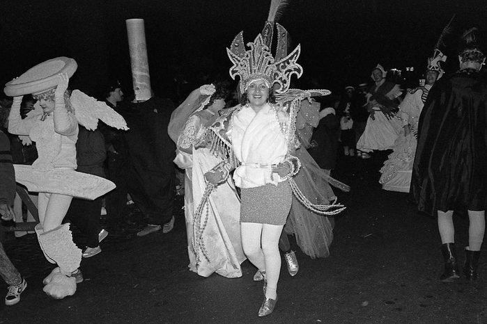 View of a woman in a Carnival costume, as she smiles and dances along 6th Avenue during New York's annual Village Halloween Parade, New York, New York, October 31, 1988.