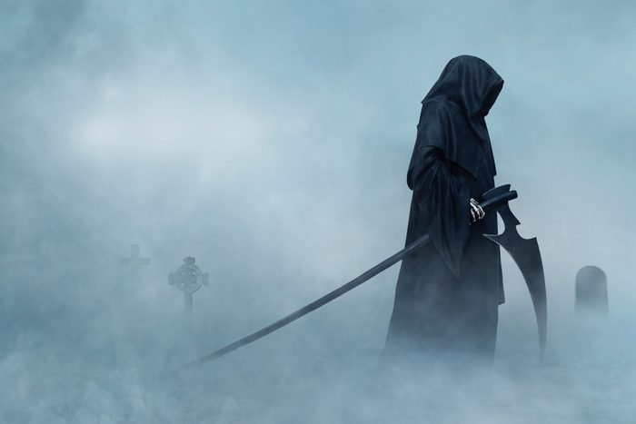 the Grim Reaper walking in a foggy cemetary.