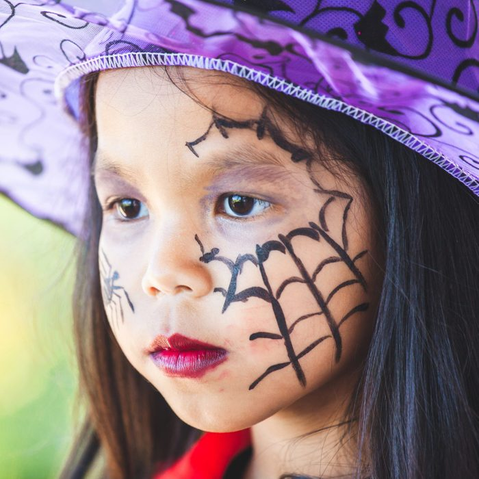 little girl with witch halloween face paint