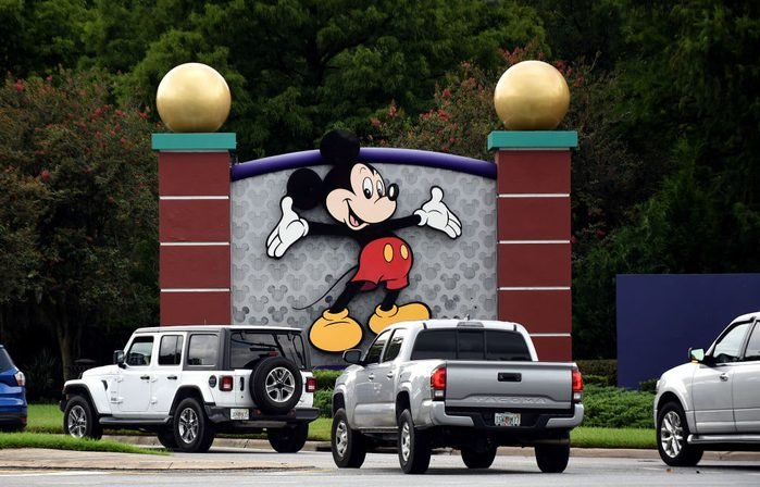 Cars drive past a sign featuring Mickey Mouse at the...