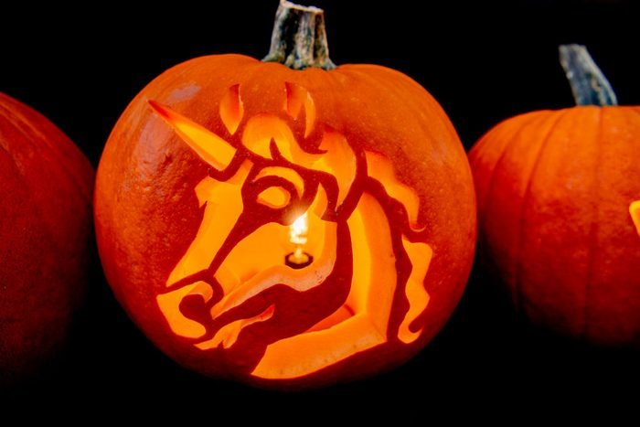 a unicorn carved into a pumpkin with a candle inside