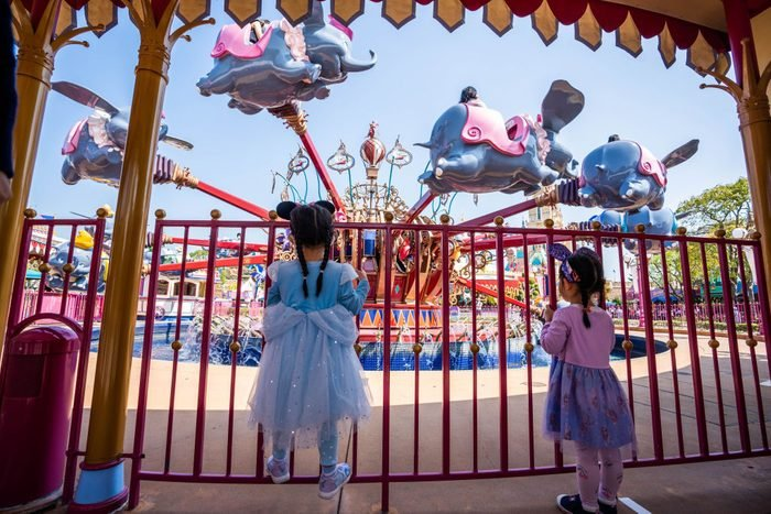 Two young girls line up for the ride of Dumbo the Flying...