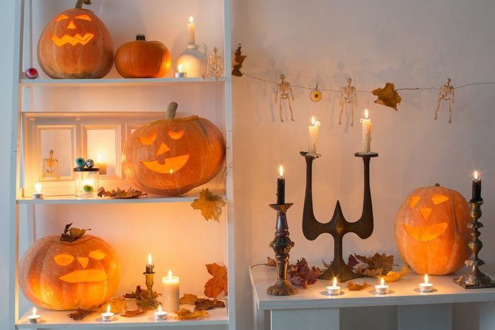 halloween pumpkins with candles and candlesticks and other halloween decor on wooden table