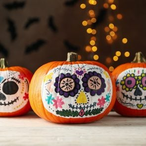 Pumpkins with catrina skull makeup on brown background with blurred lights