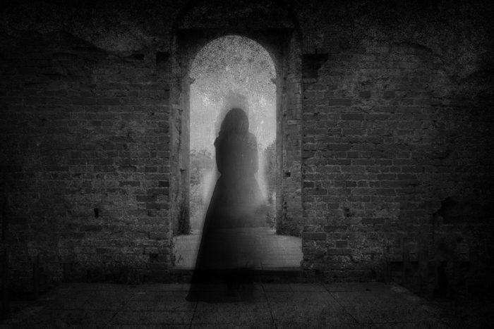 A spooky ghost of a woman in a dress, back to camera, framed by the archway of an old building. With a grunge, vintage, blurred edit.