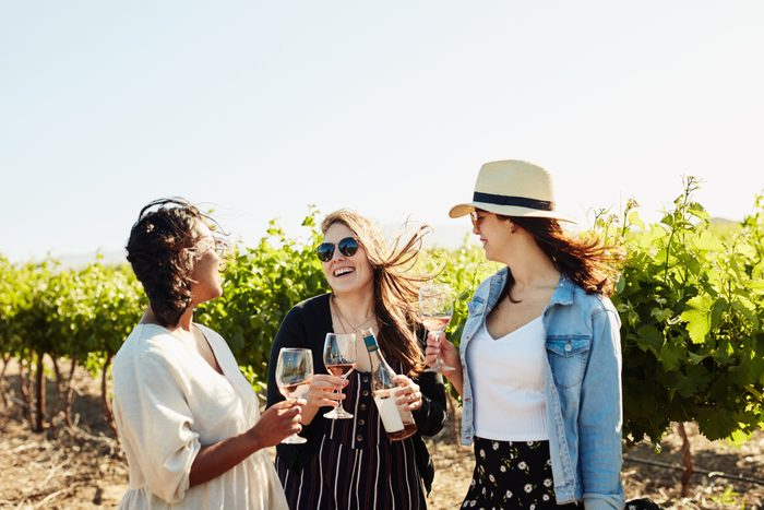 three girlfriends laughing while drinking wine at a winery vineyard
