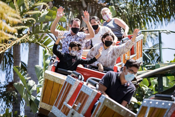 Theme park goers wear face masks as they ride a roller coaster