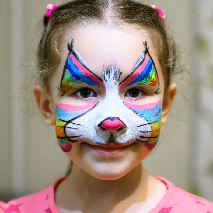 young girl with rainbow cat face paint for halloween