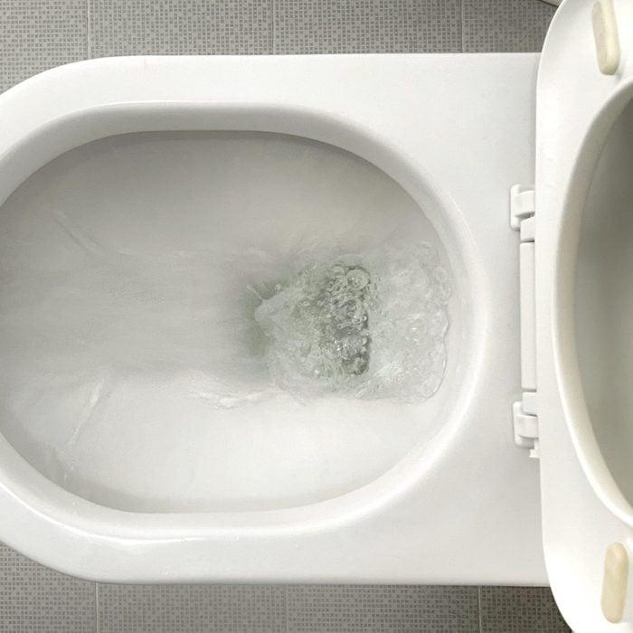 Water flushes down toilet bowl