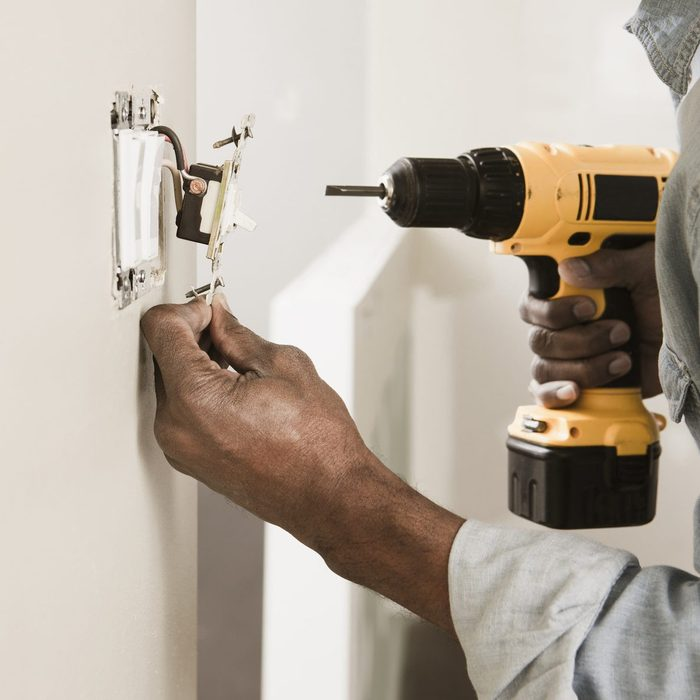 African American man using cordless drill