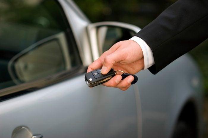 Person at car using remote control key, close-up