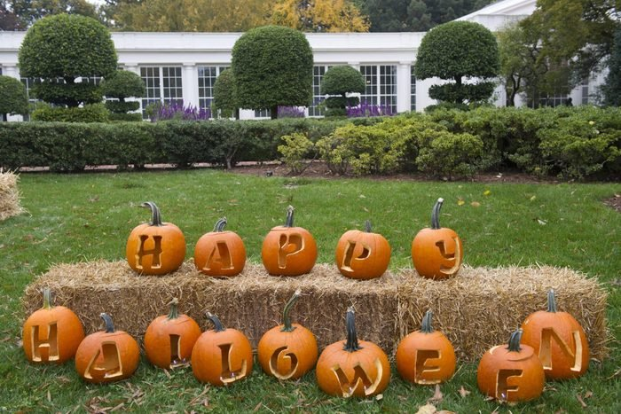 """Carved pumpkins in line spelling out """"happy Halloween"""" on front lawn"""