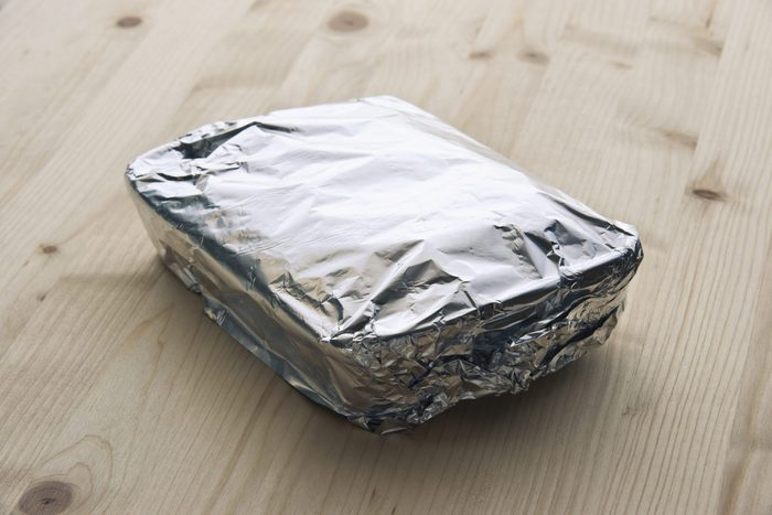 tray of leftover food covered with aluminum foil on a wood counter