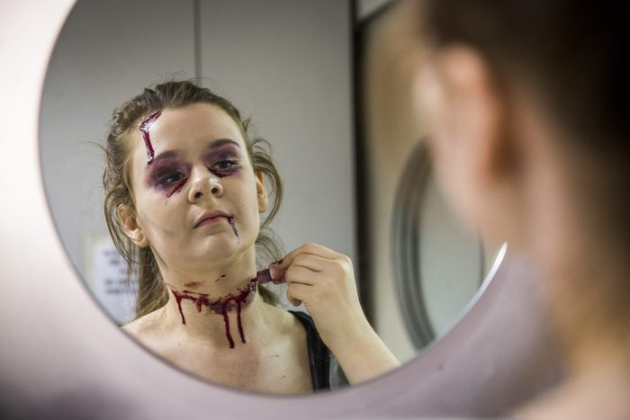 young woman applying homemade fake blood for halloween costume