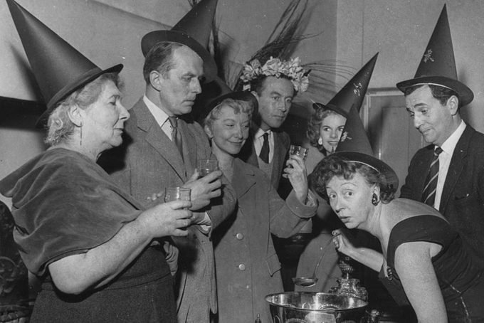 Actress Thora Hird (right, bending down) serving a witches brew punch at a Halloween party with fellow actors