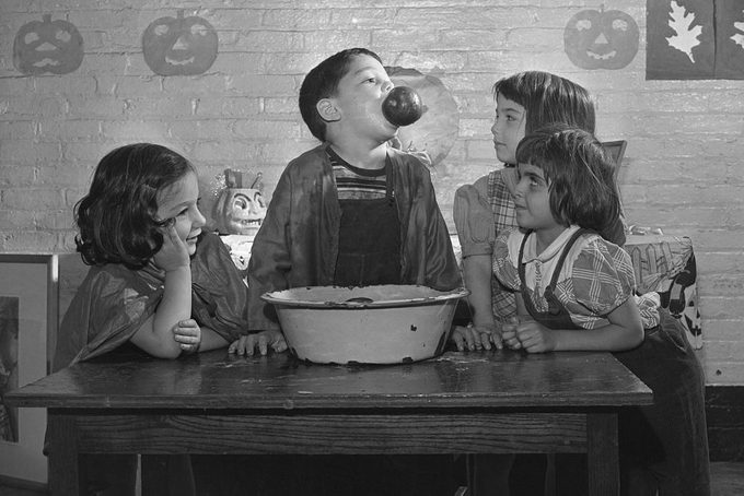children bobbing for apples at halloween party