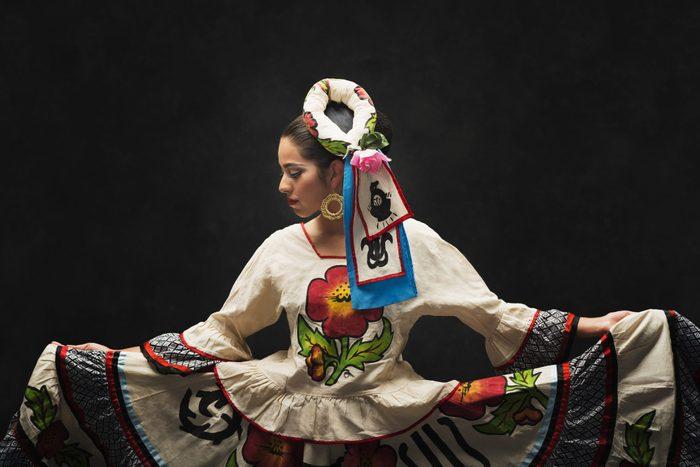 Hispanic teenage girl dancing in a Sinaloa Folkloric dress to celebrate hispanic heritage month