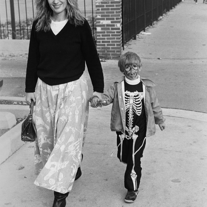 Child dressed as a skeleton for Halloween, holding a woman's hand and walking down Armitage Avenue near Halsted Street, Chicago, Illinois, October 1987.