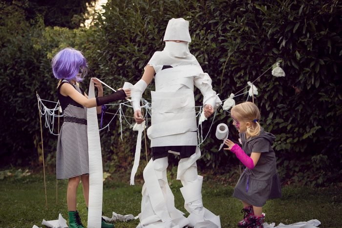 Children playing mummy wrap Halloween game