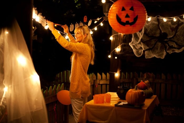 woman decorating house for halloween party
