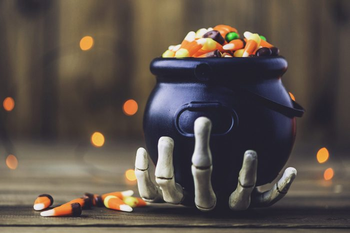 Skeleton hand holding cauldron with candy for halloween party decor