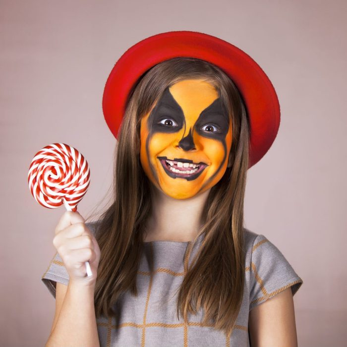 young girl with pumpkin face paint for halloween