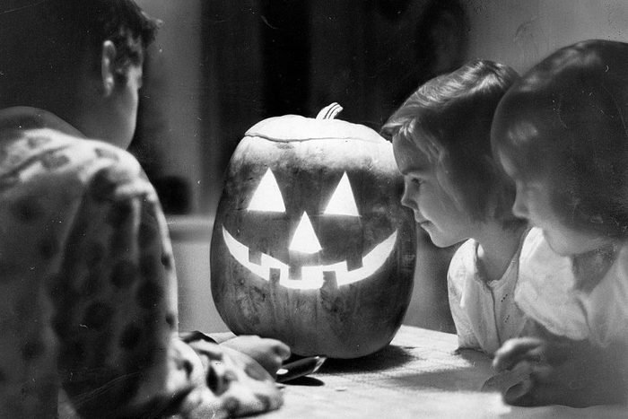 children looking at a lit up jack o lantern on halloween in 1963