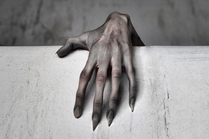 Close-Up Of Human Hand Touching Wall