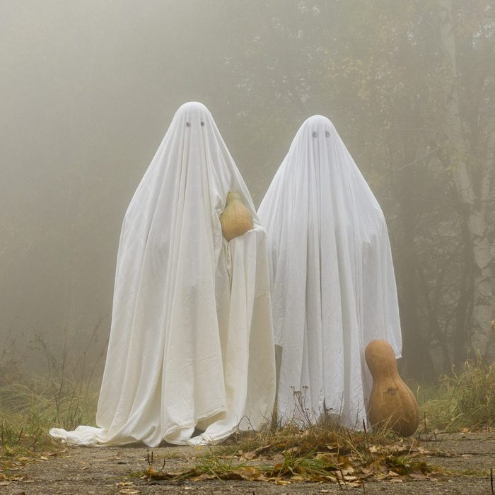 Two scary ghost halloween costumes in the woods