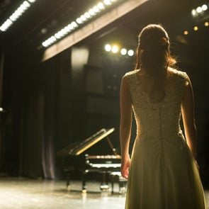 female Pianist walking towards a piano on stage